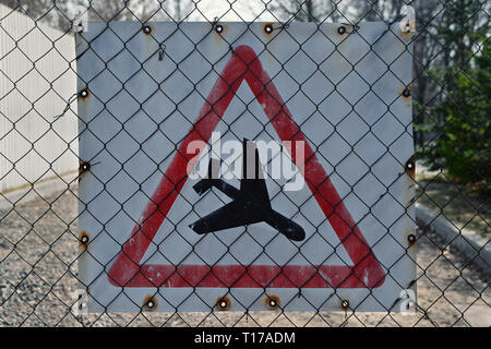 Flying airplane sign on the chain-link fencing - Stock Photo