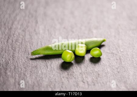 One whole green sugar snap pea pod and three peas on grey stone - Stock Photo