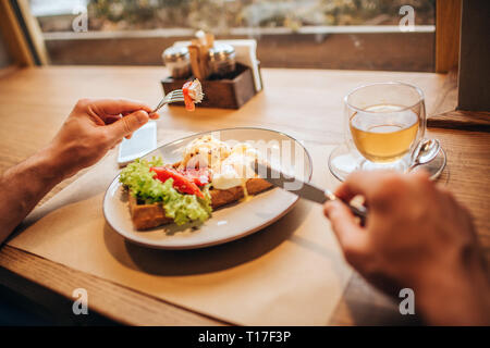 Close up of man's hands holding fork and knife. There is a plate of tasty waffle with vegetables and a cup of tea. Table is standing in front of windo - Stock Photo