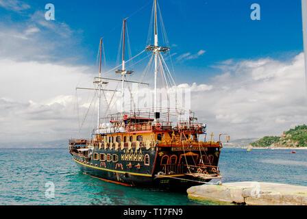 Orange beach, Sithonia, Greece - June, 12. Tourist boat in turquoise sea near of the touristic place Sarti on Sithonia peninsula of Chalkidiki in Gree - Stock Photo