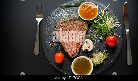 Medium rare succulent grilled beef steak served on a black board with fresh salad greens, tomato and dipping sauce viewed from overhead - Stock Photo