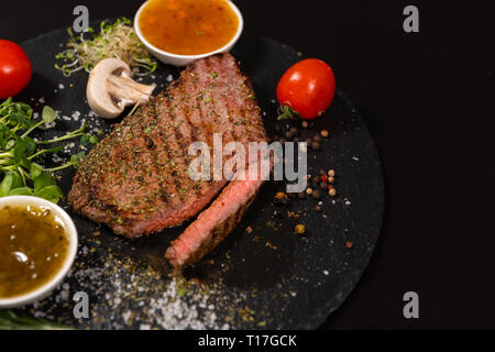 Sliced through medium rare tender grilled beef steak seasoned with herbs and spices served on a platter with fresh vegetables and sauces, high angle w - Stock Photo