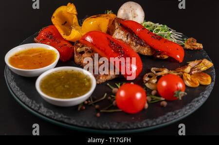 Roast red sweet peppers served with grilled pork medallions, tomato, garlic and bowls of dipping sauce - Stock Photo