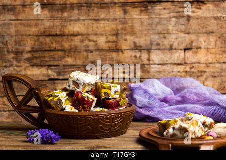 Turkish delights with pistachios and rose flower in a bowl - Stock Photo