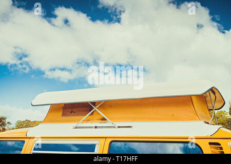 Old australian camper van with flag of Australia behind its rear window parked in caravan park on a day - Stock Photo