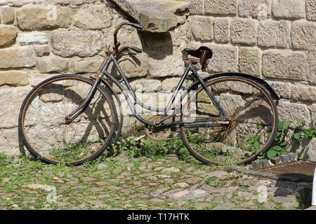 old rusty bicycle parked against a wall - Stock Photo