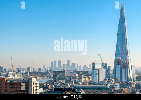 An elevated view of the Shard at London Bridge with the office blocks of Docklands & Canary Wharf in the background. - Stock Photo