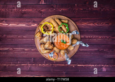 Chicken and Cheese Set for beer. Chicken wings, cheese sticks and cheese balls with bright vegetable sauce. On the cutting board and wooden background - Stock Photo