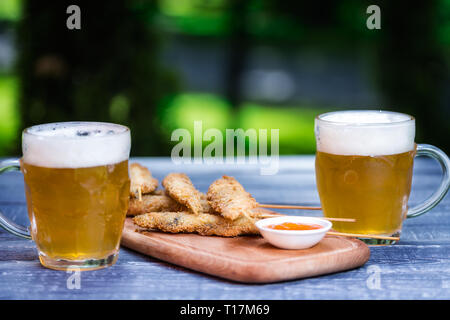 Beer snacks set. Chicken wings on sticks and two mugs of beer. On the cutting board and green summer background - Stock Photo
