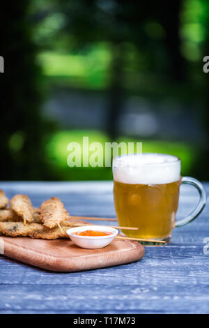 Beer snacks set. Chicken wings on sticks and mug of beer. On the cutting board and green summer background - Stock Photo