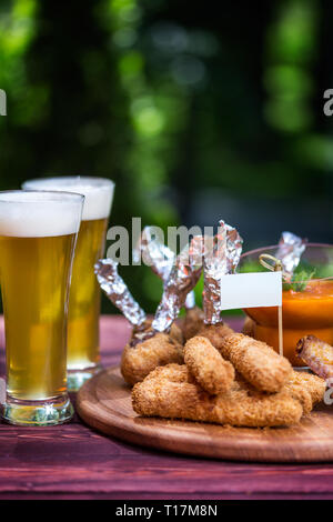 Chicken and Cheese Set for beer and two glasses of beer. Chicken wings, cheese sticks and cheese balls with bright vegetable sauce. On the cutting - Stock Photo