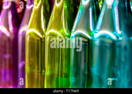Multicolored glass bottles on the shelf in the store. - Stock Photo