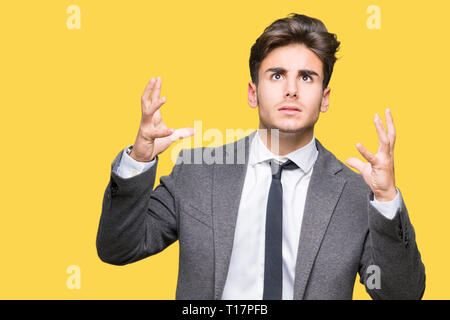 Young business man wearing suit and tie over isolated background crazy and mad shouting and yelling with aggressive expression and arms raised. Frustr - Stock Photo