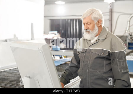 Professional engineer wearing in protective clothes, working in factory with metalwork and laser plasma cutting. Elderly bearded man operating computerized machine. - Stock Photo