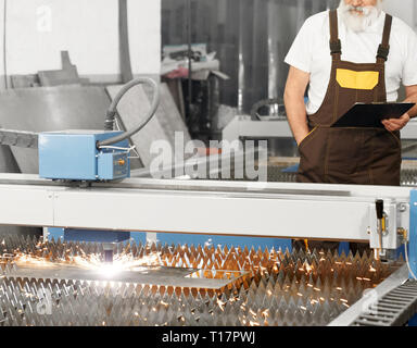CNC laser plasma cutting metal, sparks. Engineer standing behind and observing process of plasma torch cutting steel sheet. Worker wearing in coveralls, white t shirt, holding folder. - Stock Photo