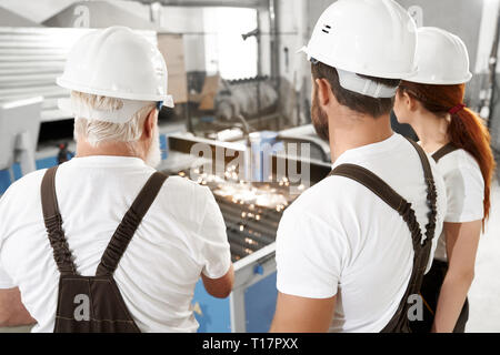 Back view of three engineers observing process of plasma laser cutting metal sheet with sparks. Workers wearing in white t shirts, white hardhats and coveralls. - Stock Photo