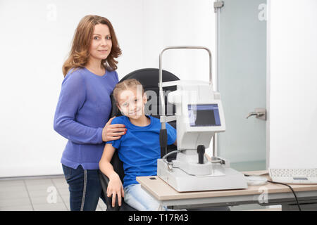 Pretty girl sitting in chair at table with modern slit lamp machine for examining eyesight. Mother and child posing in beautiful new optician office of ophthalmology clinic. - Stock Photo