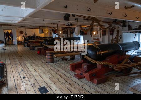 General view below deck of a line of cannon on the gun deck of HMS Warrior (1860), Portsmouth Historic Dockyard, UK. - Stock Photo