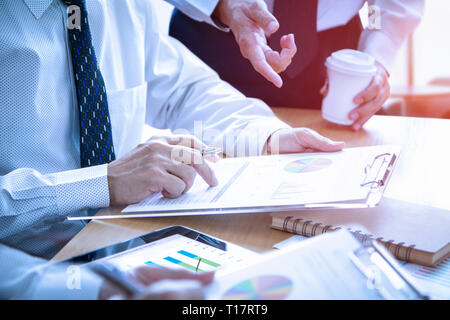 Businessmen in a meeting are deeply reviewing a financial reports for a return on investment or investment risk analysis.