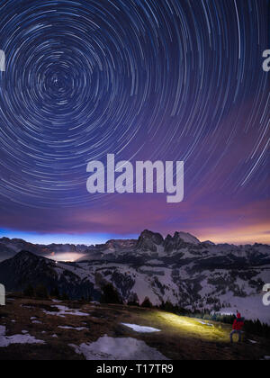 Single Hiker with headlight under starlit sky before sunrise in Mountain village Seiser Alm, Italy - Stock Photo