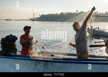 Fishermen folding fishing net on their boat in Pemuteran, Bali, - Stock Photo