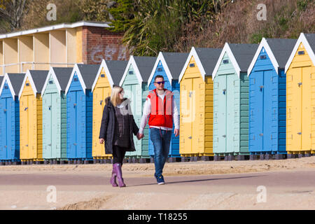 Bournemouth, Dorset, UK. 24th Mar 2019. UK weather: lovely sunny day with blue skies and warm sunshine at Bournemouth beaches, as visitors head to the seaside to make the most of the glorious weather. Couple walking hand in hand along promenade past colourful beach huts. Credit: Carolyn Jenkins/Alamy Live News - Stock Photo