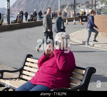 Sidmouth, UK. 24th Mar, 2019. Visitors take a good look around the seafront on a sunny day in Sidmouth. Credit: Photo Central/Alamy Live News - Stock Photo