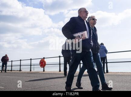 Sidmouth, UK. 24th Mar, 2019. Visitors take a walk along the seafront on a sunny day in Sidmouth. Credit: Photo Central/Alamy Live News - Stock Photo