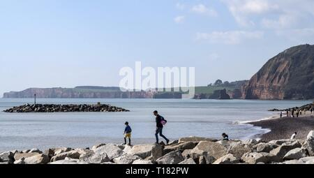 Sidmouth, UK. 24th Mar, 2019. Families playing on the rock groynes atSidmouth. Credit: Photo Central/Alamy Live News - Stock Photo