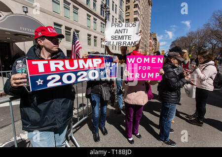 New York, USA. 24th Mar, 2019. New York, NY - 24 March 2019. Senator Kirsten Gillibrand (D-NY) held a presidential campaign rally on New York's Central Park West in Front of the Trump Hotel and Tower. Pro-Trump supporters at the entrance of the rally carry signed reading 'Trump 2020.' 'Women for Trump,' and 'Pro BDS Anti Semite Gillibrand.' BDS refers to the boycott, divestment and sanctions movement against Israel. Credit: Ed Lefkowicz/Alamy Live News - Stock Photo