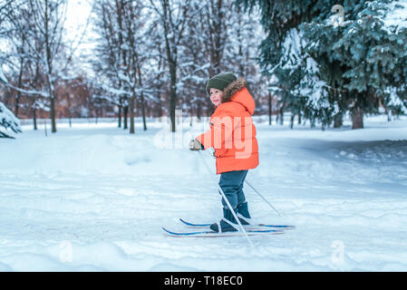 A little boy of 3-6 years old, in the winter in the city park, rides on children's skis. Free space for text. The first steps in children's sports, a - Stock Photo