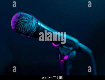 Microphone on black background with colorful pink and turquoise light. Music, concert concept. - Stock Photo