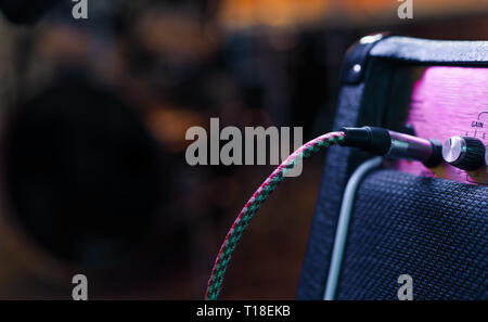 Part of guitar amp with plug in cable. Music concert or recording concept. Copy space - Stock Photo