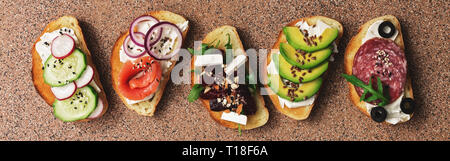 Set with toast bread and different toppings, salmon, smoked sausage, vegetables and feta cheese on a brown stone background. Top view - Stock Photo