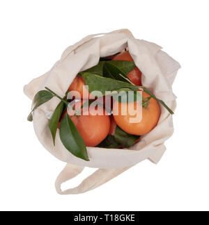Fresh picked oranges in reusable, recyclable fabric shopping tote bag, isolated on white. For environmentally friendly, green consumers.Overhead view. - Stock Photo
