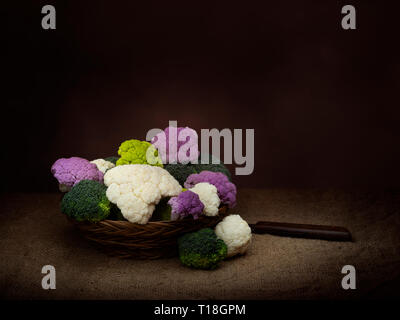 Naturally colourful vegetables in basket, chiaroscuro style dark still life. Assorted raw cauliflower, with broccoli florets. Healthy assortment. - Stock Photo