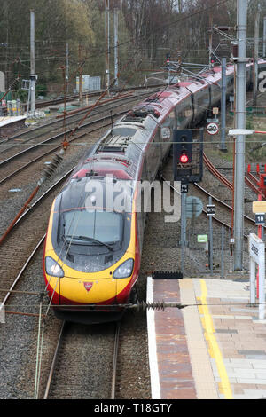 Class 390 Pendolino electric multiple unit train operated by Virgin West Coast arriving at Lancaster station on West Coast Main Line, 21st March 2019. - Stock Photo
