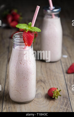 Healthy strawberry smoothie, milk shake, in traditional bottles with scattered berries and straw over a wood background. Vertical composition - Stock Photo