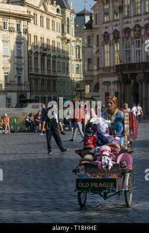 Prague, Czech Republic - September 10, 2019: Street vendor woman with a souvernirs car sells remenbrances in the old city plaza - Stock Photo