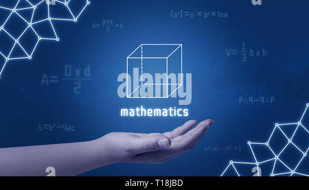 Concept of mathematics. Cube in hand surrounded by mathematical formulas and an computer network concept. - Stock Photo