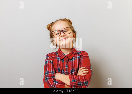 Portrait of a funny little preschool child girl in glasses on gray background. Concept education. Back to school. - Stock Photo
