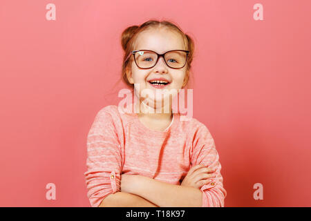 Portrait of nice-looking cute adorable cheerful cheery content modern little child girl folded arms in glasses over pink background - Stock Photo