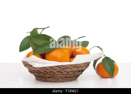 Juicy tangerines, small oranges with leaves in wicker basket with serviette, napkin. Fresh fruit on white, isolated against background. - Stock Photo