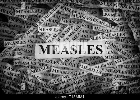 Measles. Torn pieces of paper with the words Measles. Concept image. Black and White. Close up. - Stock Photo