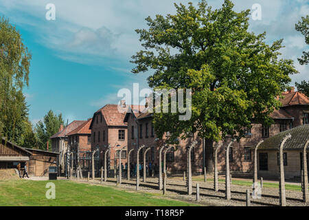 Oswiencim, Poland - September 21, 2019: Tourists going trought the gate of the nazi concentration camp of Auschwitz  - Stock Photo