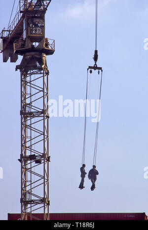 Archive of two men workers in harness suspended & lowered by crane on shipping containers in depot & connect cable for lifting East London England UK - Stock Photo