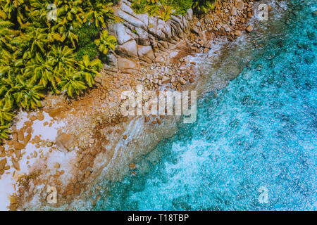 Aerial drone helicopter view of crystal clear turquoise water and amazing granite rocks. La Digue Island Seychelles