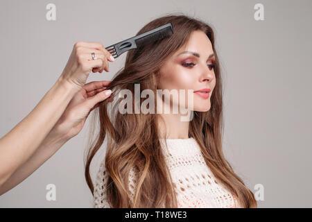 Elegant woman with makeup preparing for shooting in studio. - Stock Photo