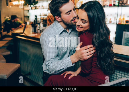 Lovely picture of handsome man and beautiful woman sitting very close together. He is holding her on her hands and trying ti kiss her. She is smiling  - Stock Photo
