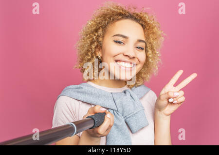 Smiling girl is taking a selfie. She uses a selfie sticj for that. Young woman is posing and showing the piece symbol to camera. Isolated on pink back - Stock Photo